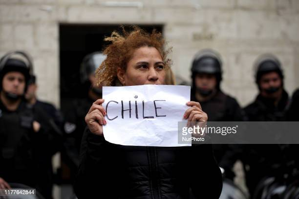 Leftwing activists gather and shout slogans during a rally to show solidarity with protesters in Chile at the Chilean Consulate General on October 22...
