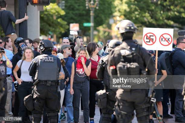 Leftwing counterprotesters look on as rightwing demonstrators hold a rally supporting gun rights and free speech on August 4 2018 in Portland Oregon...