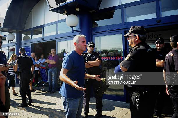 Leftwing group Sindicato Andaluz de Trabajadores spokesman Diego Canamero speaks to police outide a supermarket during a Robin Hood like action where...