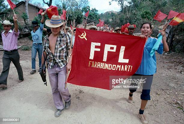 Left-wing guerrillas from the Fuerzas Populares de Liberación, FPL, march behind a banner along a road in Santa Anita, Chalatenango department, El...