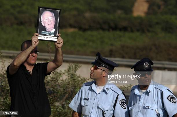 A leftwing Israeli activist holds a portrait of former Israeli prime minister Yitzhak Rabin during the circumcision of the son of Israeli assassin...