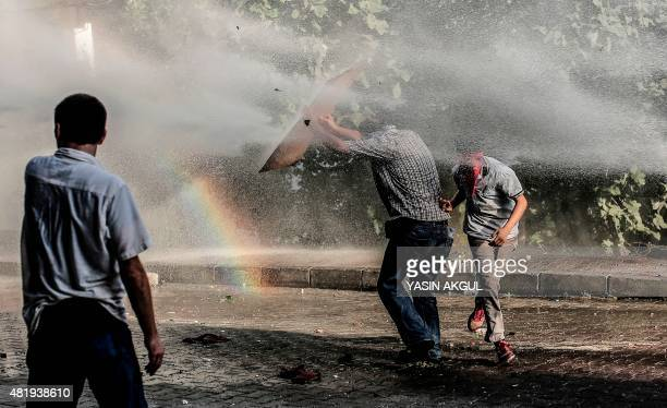 Leftwing militants take cover from a water cannon during clashes with Turkish police officers on July 25 2015 at Gazi district in Istanbul Turkey's...