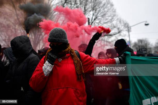 A leftwing protester holds a banner while others burn colour flares during a protest march during todays AfD federal congress at the Hannover...