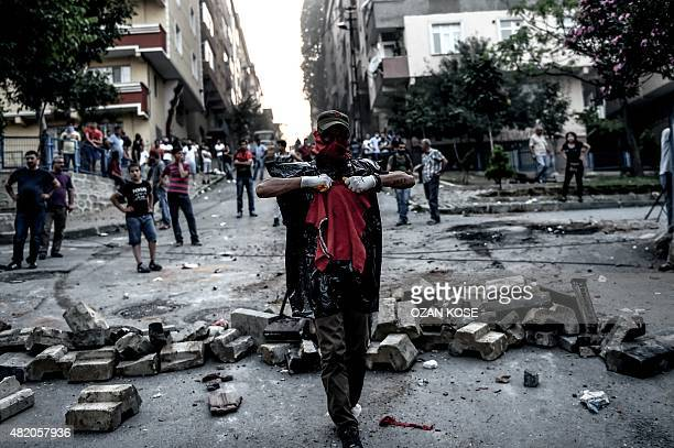 Left-wing protesters gather near a barricade during clashes with Turkish riot police in the district of Gazi in Istanbul, on July 26, 2015. A Turkish...
