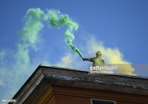 TOPSHOT Leftwing protesters light flares on a rooftop overlooking a demonstration against capitalism in Berlin's Wedding district on the eve of...