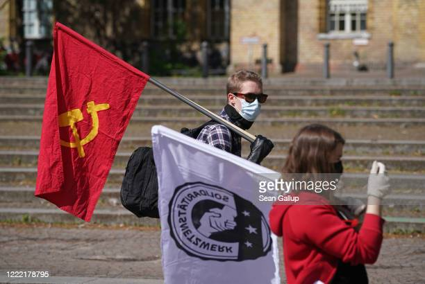 Leftwing protesters wearing protective face masks demonstrate on Mariannenplatz while maintaining social distancing on May Day during the novel...