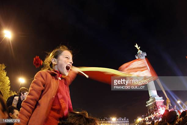 A leftwing supporter waves a campaign flag as she celebrates on May 6 2012 the victory of France's Socialist Party newlyelected president Francois...