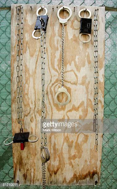 Leg irons and hand cuffs hang on a board at Camp Delta at Guantanamo Naval Base August 23, 2004 in Guantanamo, Cuba. On August 24, preliminary...