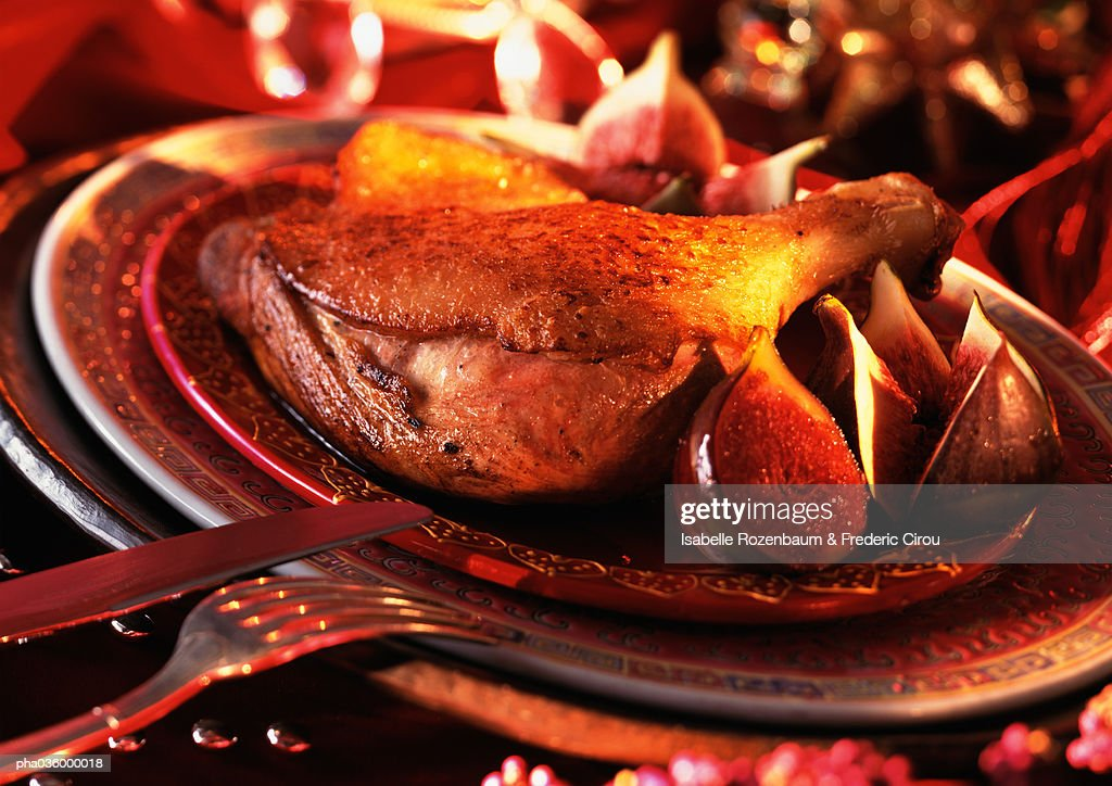 Leg of duck with figs on plate, close-up : Stockfoto