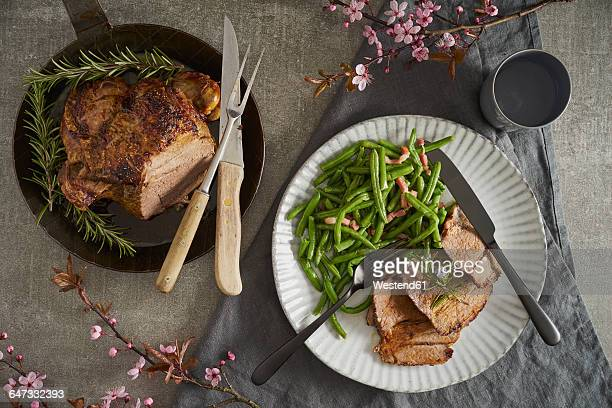 Leg of lamb with rosemary, green beans and bacon on plate
