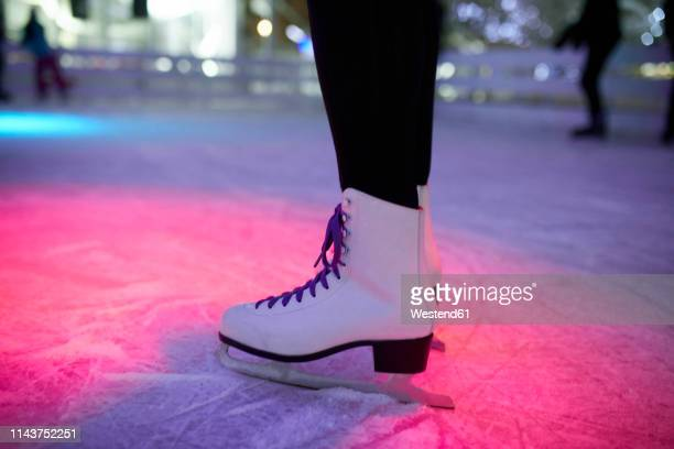 leg of woman wearing ice skates standing on an ice rink - ice rink stock pictures, royalty-free photos & images