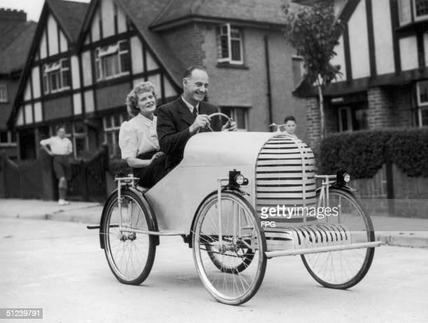Mr and Mrs Dado make their way down an English street in their cycle-powered car.