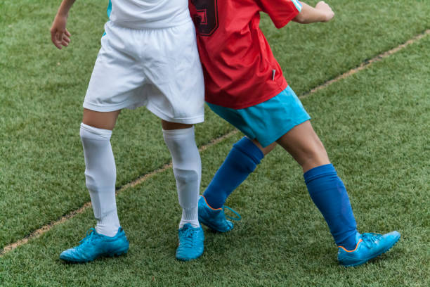 Leg shot of two boys, from rival teams playing soccer