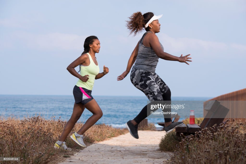 Leg workout doing bench taps exercise. Fat and slim women exercising outdoors on the seacoast. : Stock Photo