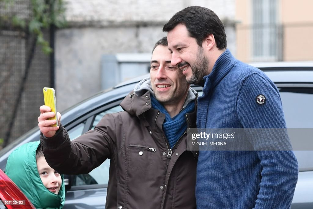 Lega Nord far right party leader Matteo Salvini (R), poses for a selfie with a supporter as he arrives to vote for general elections at a polling station on March 4, 2018 in Milan. Italians vote today in one of the country's most uncertain elections, with far-right and populist parties expected to make major gains. / AFP PHOTO / Miguel MEDINA