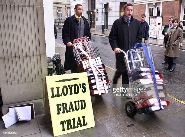 Legal clerks wheel carts loaded with files past the entrance of the courts on Chancery Lane where the hearing alleging fraud by Lloyd's of London is...