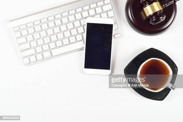 Legal concept shot of computer keyboard, smartphone, black tea and judges gravel