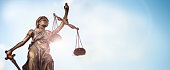 Legal law concept statue of Lady Justice with scales of justice sky background