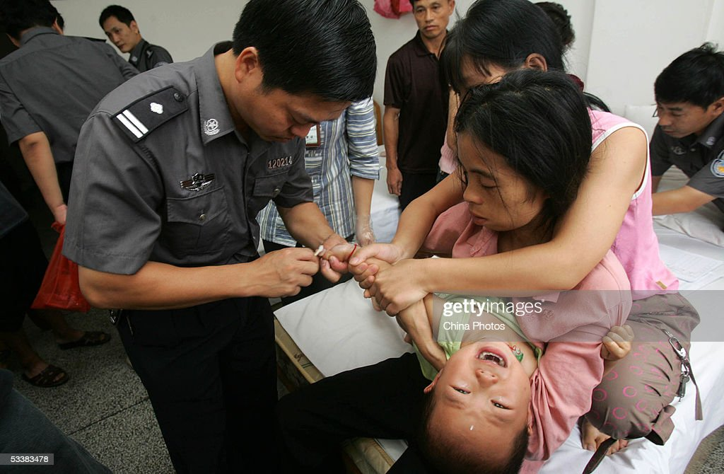 A legal medical expert of the police gets a blood sample of the son of a trapped miner for a DNA test August 13, 2005 in Xingning of Guangdong province, south China. Rescue operations have made little progress at the flooded Daxing Colliery where 122 miners are still trapped underground, according to the rescue headquarters. According to engineers at the site, water levels in the tunnel have not dropped because the flood is gushing in fast and the narrow tunnels cause great troubles to install more pumps. Local government has started to organize the family members of trapped miners to provide blood sample for DNA tests.