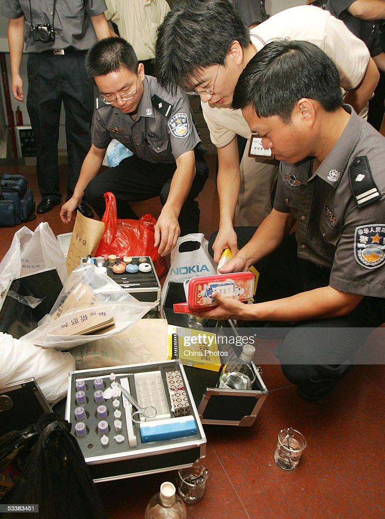 Legal medical experts of the police prepare to get blood sample of family members of trapped miners for DNA test August 13, 2005 in Xingning of Guangdong province, south China. Rescue operations have made little progress at the flooded Daxing Colliery where 122 miners are still trapped underground, according to the rescue headquarters. According to engineers at the site, water levels in the tunnel have not dropped because the flood is gushing in fast and the narrow tunnels cause great troubles to install more pumps. Local government has started to organize the family members of trapped miners to provide blood sample for DNA tests.