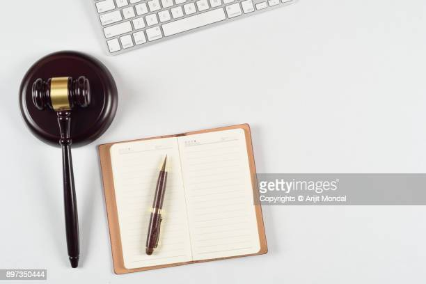 Legal proceeding concept with gavel, computer keyboard, notebook, pen with top view copy space