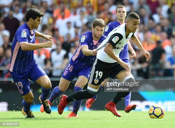 Leganes' Argentinian defender Ezequiel Munoz and Leganes' Serbian midfielder Darko Brasanac vie with Valencia's Spanish forward Rodri during the...