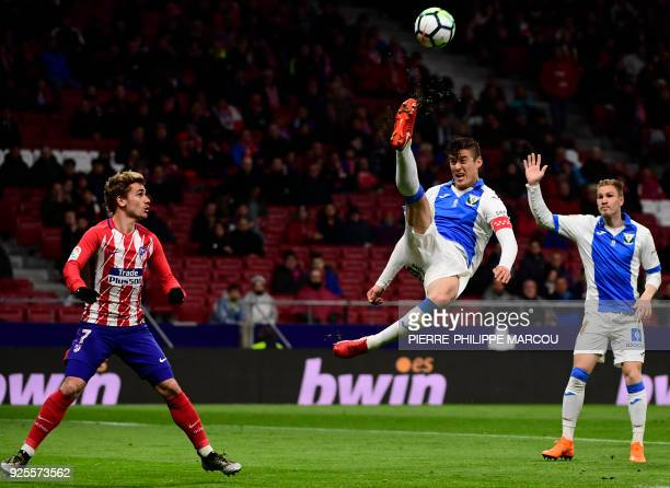 Leganes' Argentinian defender Martin Mantovani kicks the ball beside Atletico Madrid's French forward Antoine Griezmann during the Spanish league...