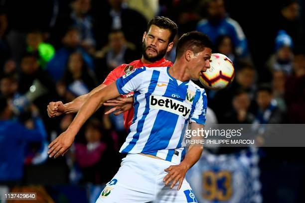 Leganes' Argentinian forward Guido Carrillo and Real Madrid's Spanish defender Nacho Fernandez jump for the ball during the Spanish league football...