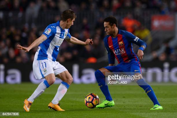 Leganes' Argentinian midfielder Alexander Szymanowski vies with Barcelona's Brazilian forward Neymar during the Spanish league football match FC...
