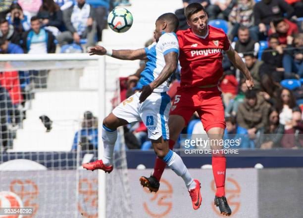 Leganes' Guadeloupean forward Claudio Beauvue jumps for the ball with Sevilla's French defender Clement Lenglet during the Spanish League football...