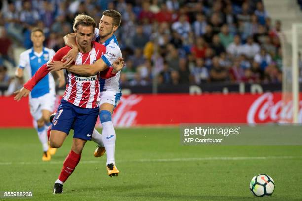 Leganes' midfielder Ruben Perez commits a foul against Atletico Madrid's forward from France Antoine Griezmann during the Spanish league football...