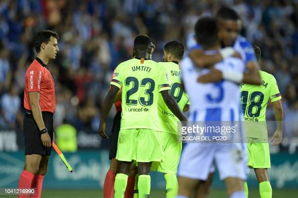 Leganes players celebrate their win as Barcelona players protest to the referee at the end of the Spanish league football match Club Deportivo...