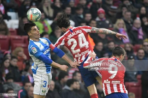 Leganes' Spanish defender Unai Bustinza, Atletico Madrid's Croatian defender Sime Vrsaljko and Atletico Madrid's Spanish forward Alvaro Morata jump...