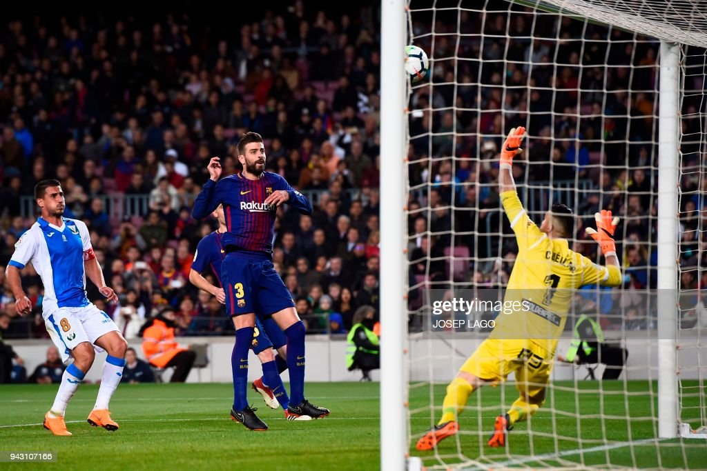 Leganes' Spanish goalkeeper Pichu Cuellar (R) prepares to block a shot on goal by Barcelona's Spanish defender Gerard Pique (C) next to Leganes' Brazilian midfielder Gabriel Appelt (L) during the Spanish league football match between FC Barcelona and Leganes t the Camp Nou stadium in Barcelona on April 7, 2018. / AFP PHOTO / Josep LAGO