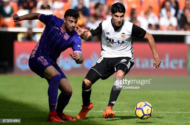 Leganes' Spanish midfielder Diego Rico vies with Valencia's Spanish midfielder Carlos Soler during the Spanish league footbal match Valencia CF vs...