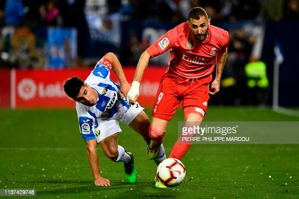 Leganes' Spanish midfielder Javier Eraso challenges Real Madrid's French forward Karim Benzema during the Spanish league football match between Club...