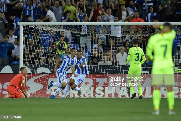 Leganes' Spanish midfielder Oscar Rodriguez celebrates his team's second goal with Barcelona's Spanish midfielder Carles Alena during the Spanish...