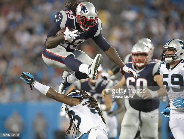 LeGarrette Blount of the New England Patriots jumps over Tre Boston of the Carolina Panthers during their game at Bank of America Stadium on August...