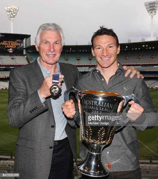 Legend AFL coach Michael Malthouse poses with the Jock McHale medal and AFL games record holder Brent Harvey poses with the AFL Premiership Cup...