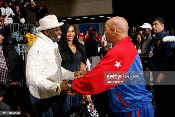 NFL legend Deion Sanders shakes hands with Harlem Globetrotters legend Fred Curly Neal during the 2010 NBA AllStar Celebrity Game presented by FINAL...