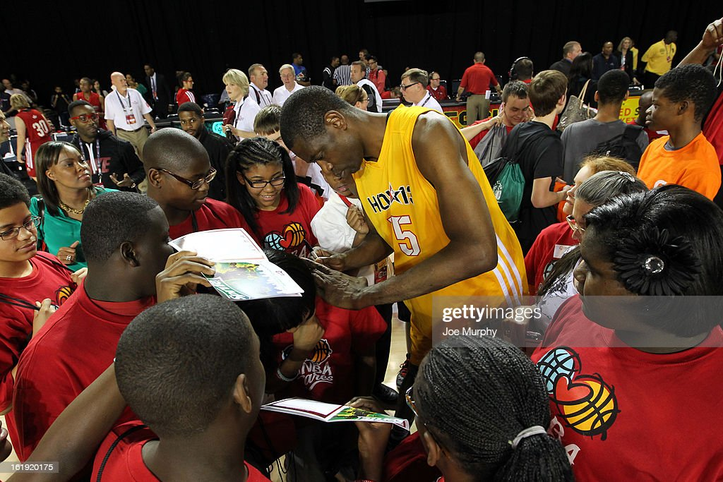 NBA Legend Dikembe Mutombo signs an autograph during the NBA Cares Special Olympics Unity Sports Basketball Game on Center Court during the 2013 NBA Jam Session on February 17, 2013 at the George R. Brown Convention Center in Houston, Texas.