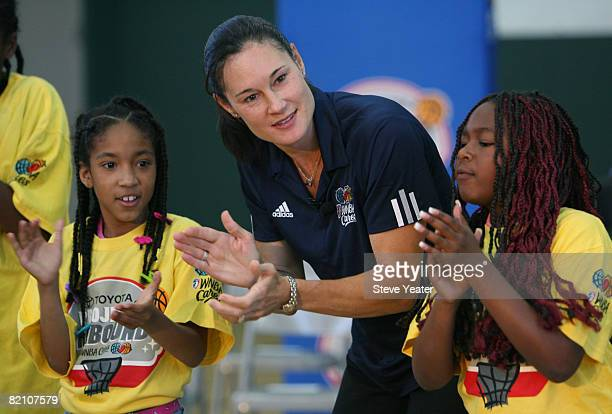 WNBA legend Jennifer Azzi gets some help pumping up the crowd from Destiny Davis and Zharia Buchanan before the dedication of a new learning center...