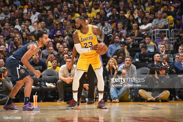NBA legend Kobe Bryant looks on as LeBron James of the Los Angeles Lakers dribbles the ball against the Denver Nuggets on October 25 2018 at STAPLES...