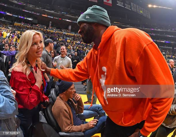 Legend Kobe Bryant speaks with President of the Los Angeles Lakers Jeanie Buss during the Dallas Mavericks game against the Los Angeles Lakers on...