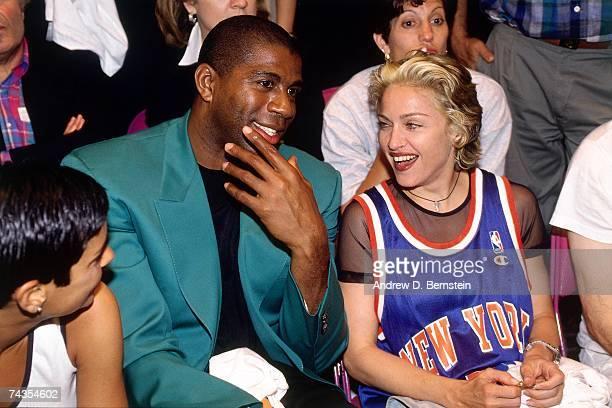 Legend Magic Johnson and singer Madonna talk while they watch Game Four of the NBA Finals played on June 15 1994 at Madison Square Garden in New York...