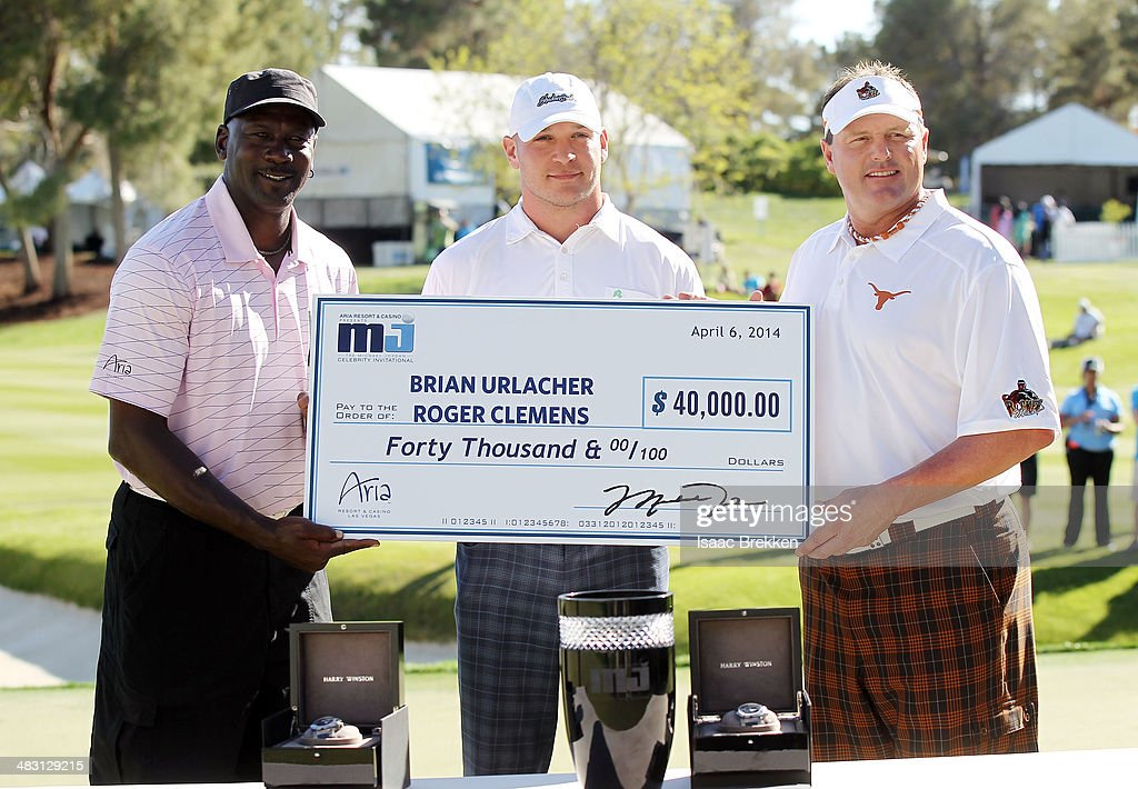 NBA legend Michael Jordan (L) presents former NFL player Brian Urlacher and Roger Clemens with a check for $40,000 after they won Aria Resort & Casino's 13th Annual Michael Jordan Celebrity Invitational at Shadow Creek on April 6, 2014 in North Las Vegas, Nevada.