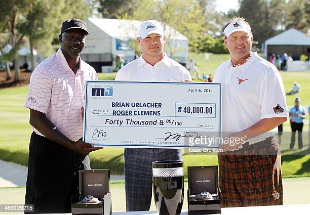 NBA legend Michael Jordan presents former NFL player Brian Urlacher and Roger Clemens with a check for $40000 after they won Aria Resort Casino's...