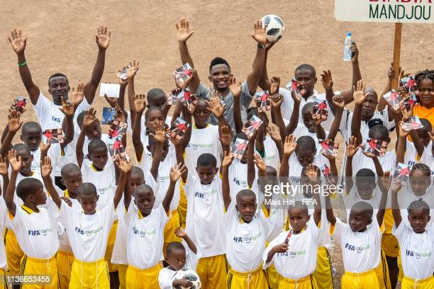 Legend Samuel Eto'o poses for a group photo with children during his visit in school event organized by FIFA Foundationsupported NGO Sport and...