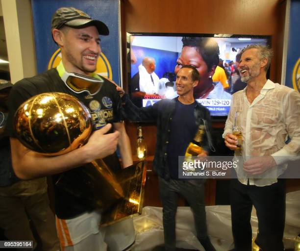 NBA legend Steve Nash and Klay Thompson with Bruce Fraser of the Golden State Warriors celebrate with the Larry O'Brien Trophy in the locker room...