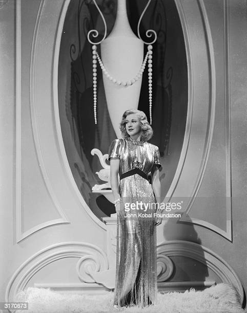 Legendary American actress and dancer Ginger Rogers wearing a fulllength evening dress in a metallic fabric